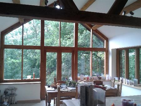 Oak frame kitchen extension with exposed oak truss and purlins and glazed oak porch.